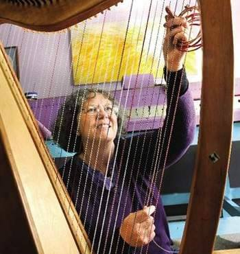 Laurie Nielsen, owner of Markwood Heavenly Strings & Cases, restringing a harp, replacing harp strings with Markwood custom harp strings